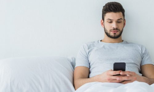 Man alone in bed, reading about sleep training on the phone