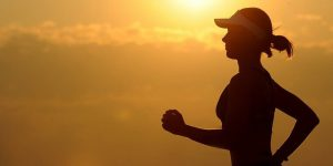 woman running in against golden sun - the answer to how to sleep better